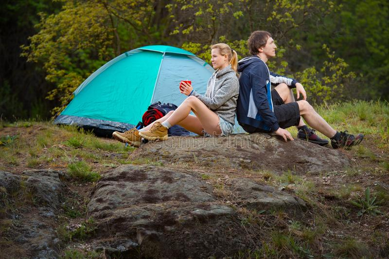 Couple hikers in the wild forest. Man and woman resting with cup royalty free stock image