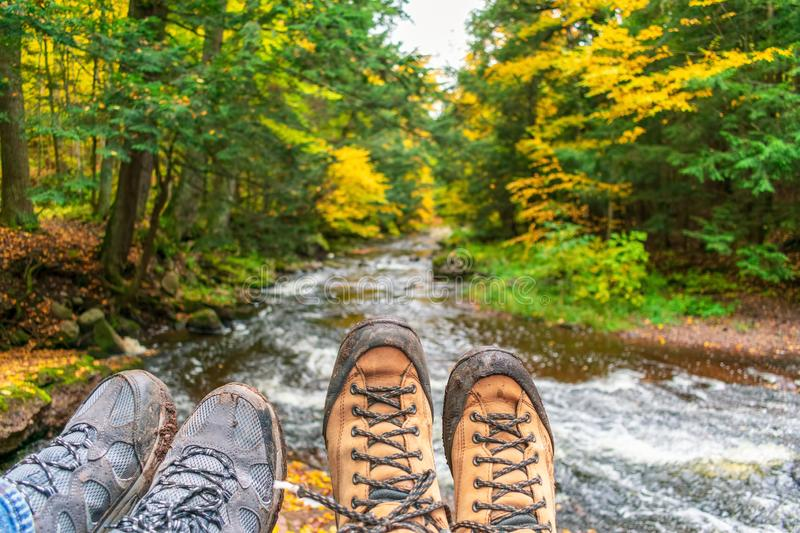 Couple hiking - muddy boots over forest stream. Couple hiking, muddly hiking boots over forest stream in fall stock photos