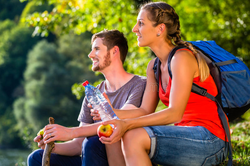 Couple hiking in summer drinking water stock photos