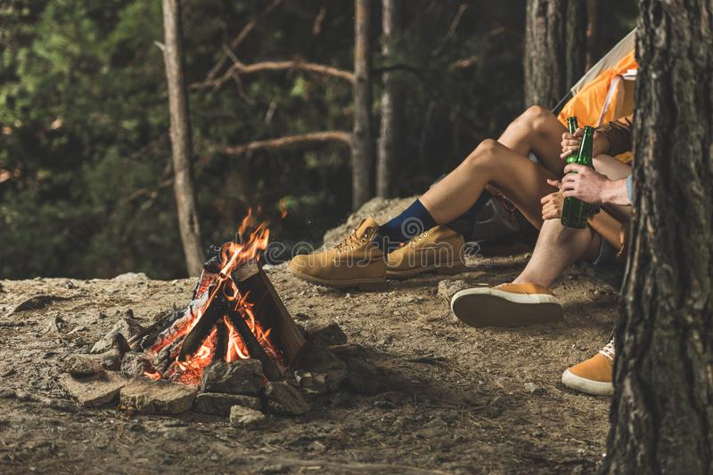Couple on hiking trip drinking beer while sitting next. To campfire royalty free stock photography