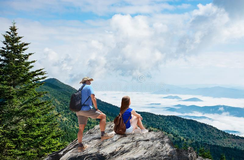 Couple enjoying beautiful view on summer mountain trip. royalty free stock images