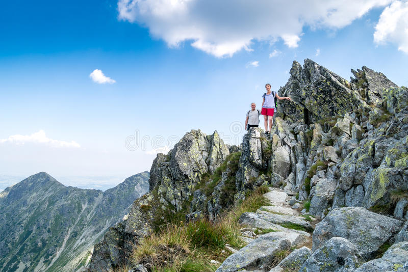 Couple hiking up in the mountains stock photo