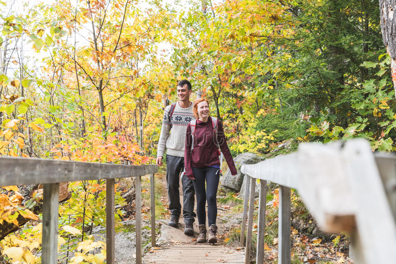 Couple hiking in the woods in autumn stock photo