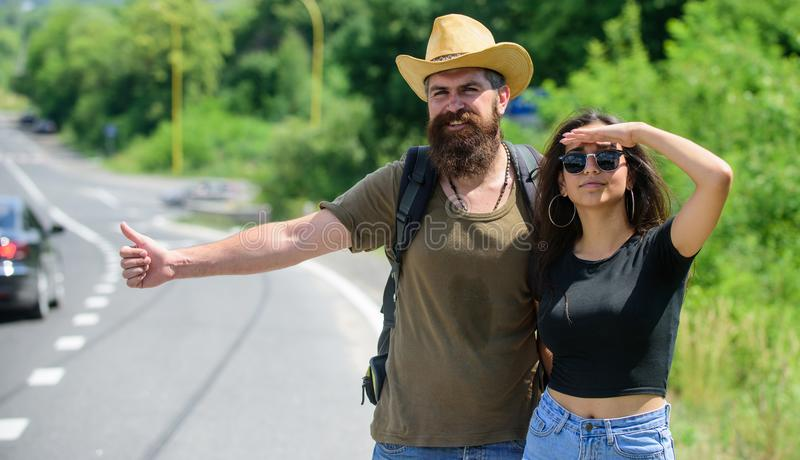 Couple hitchhikers travelling summer sunny day. Couple travelers man and girl hitchhiking at edge road nature background royalty free stock photo