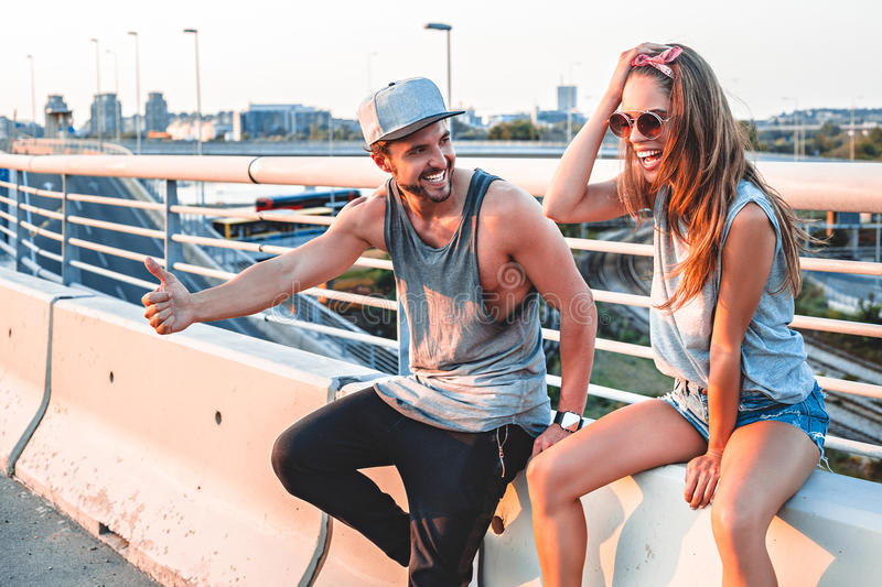 Couple hitchhiking and laughing royalty free stock photo