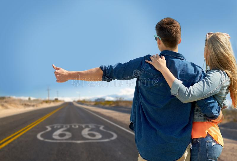 Couple hitchhiking over us route 66 in america. Road trip, hitchhike, travel and gesture concept - happy couple hitchhiking over us route 66 background royalty free stock images