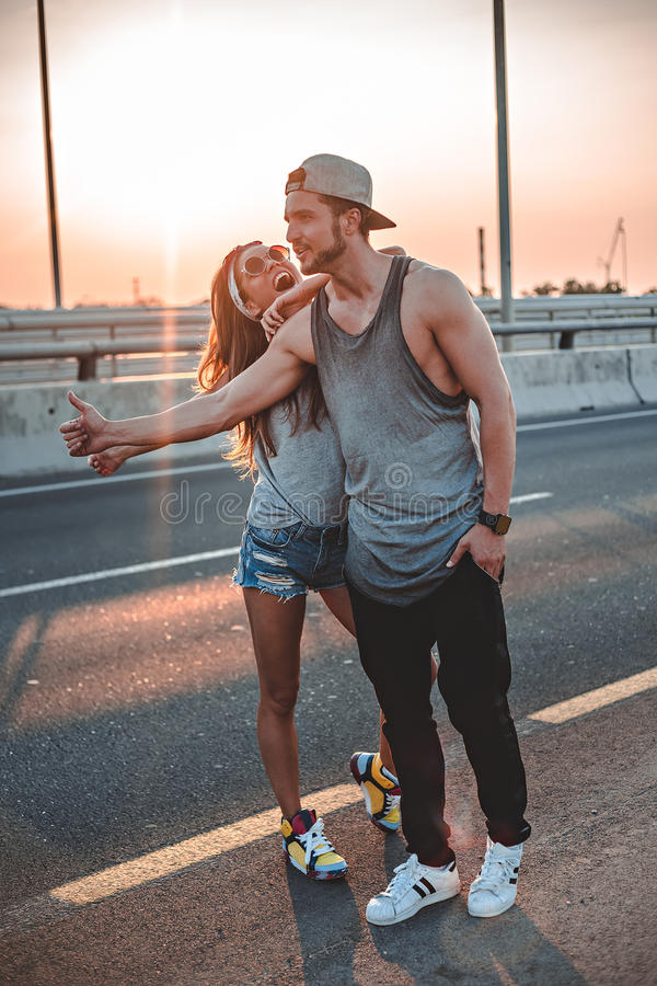 Couple hitchhiking. On the road royalty free stock images