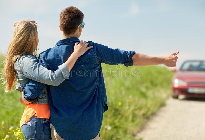 Couple hitchhiking and stopping car on countryside. Road trip, hitchhike, travel, gesture and people concept - happy couple hitchhiking and stopping car at royalty free stock photo