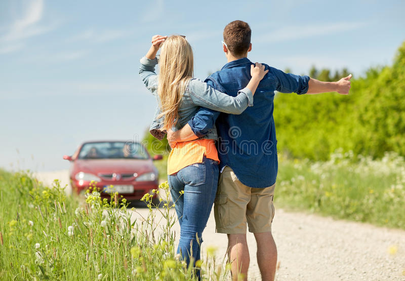 Couple hitchhiking and stopping car on countryside. Road trip, hitchhike, travel, gesture and people concept - happy couple hitchhiking and stopping car at royalty free stock images