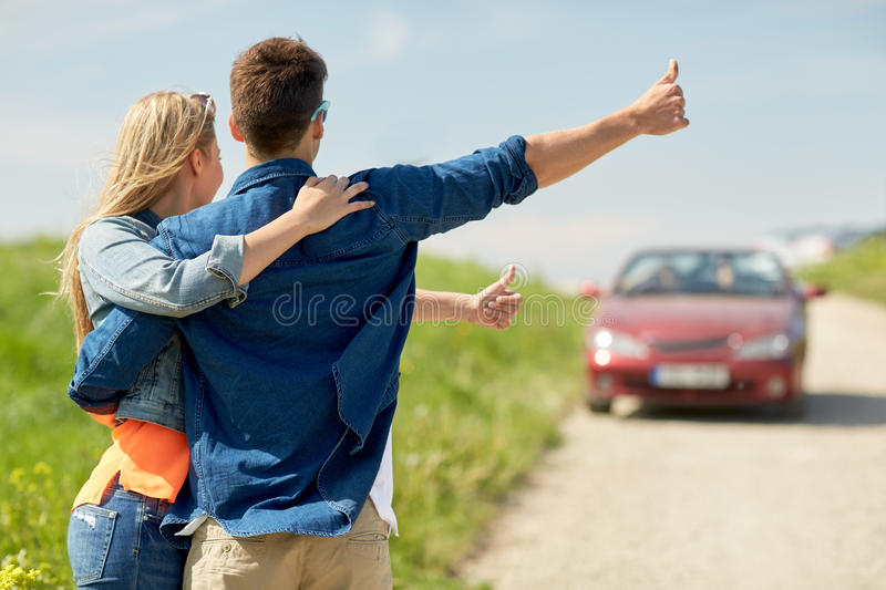 Couple hitchhiking and stopping car on countryside. Road trip, hitchhike, travel, gesture and people concept - happy couple hitchhiking and stopping car at stock image
