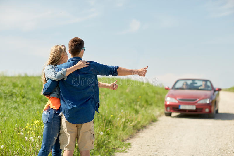 Couple hitchhiking and stopping car on countryside. Road trip, hitchhike, travel, gesture and people concept - happy couple hitchhiking and stopping car at royalty free stock photos
