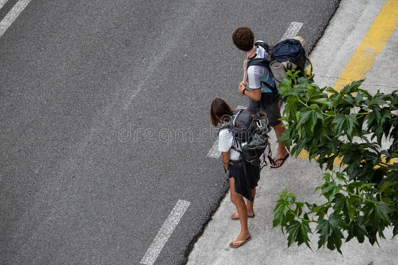 Couple hitchhiking to Finisterre, Spain. Hitching concept. Santiago de Compostela, Spain; september 19, 2019: Couple hitchhiking to Finisterre, Spain. Hitching stock photo