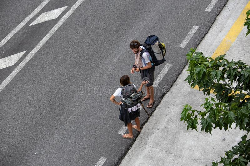 Couple hitchhiking to Finisterre, Spain. Hitching concept. Santiago de Compostela, Spain; september 19, 2019: Couple hitchhiking to Finisterre, Spain. Hitching stock photos