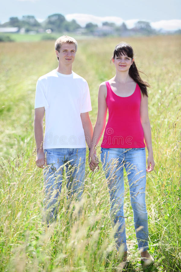 Couple hold hands in field near village