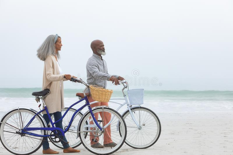 Couple holding bicycles by the beach stock photo