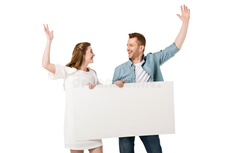 Happy young couple holding blank banner while standing with raised hands and smiling each other. Isolated on white stock photo