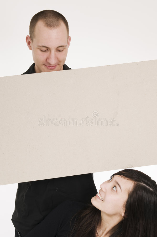 Couple holding a blank sign. Young couple holding a blank sign stock image