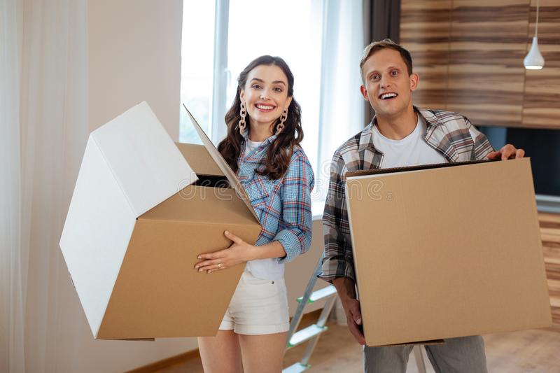 Couple holding boxes with things while moving to new house royalty free stock photo
