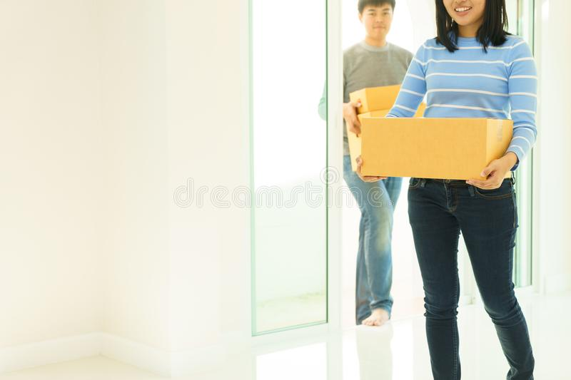 Couple holding boxes and walking together - moving house concept stock images