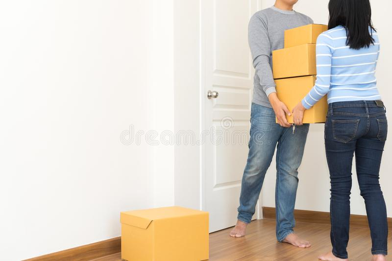 Couple holding boxes and walking together - moving house concept stock photo