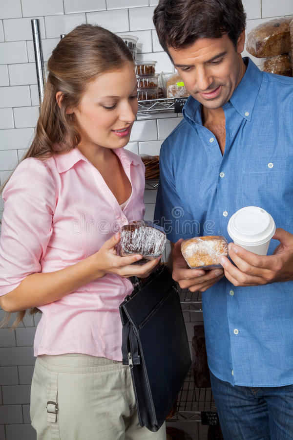 Download Couple Holding Cakes And Coffee Cup At Grocery Stock Photo - Image: 37111926