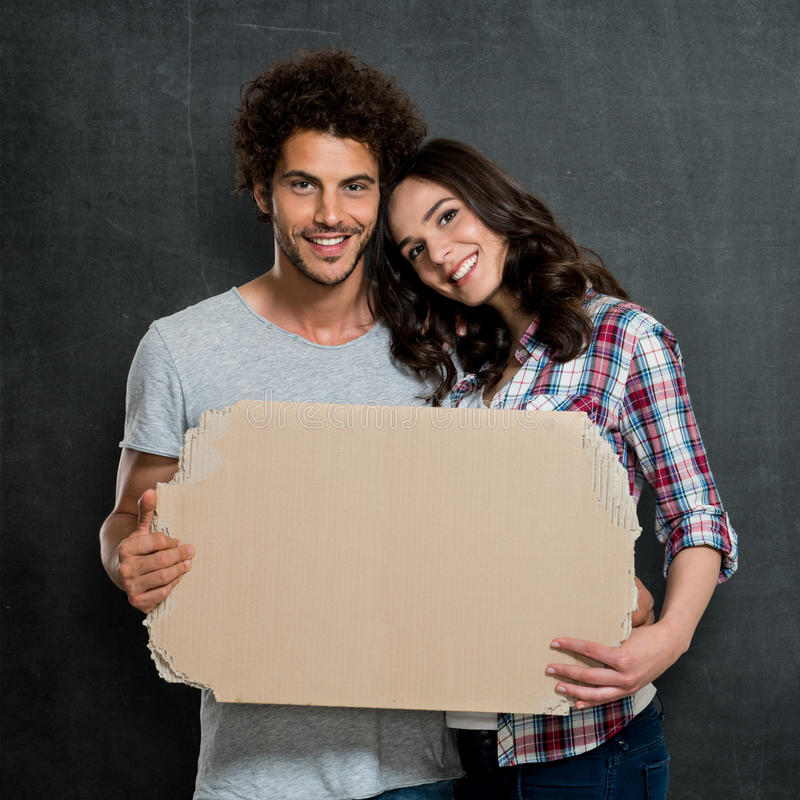 Couple Holding Cardboard Banner. Young Beautiful Couple Holding Cardboard Over Gray Background stock photography