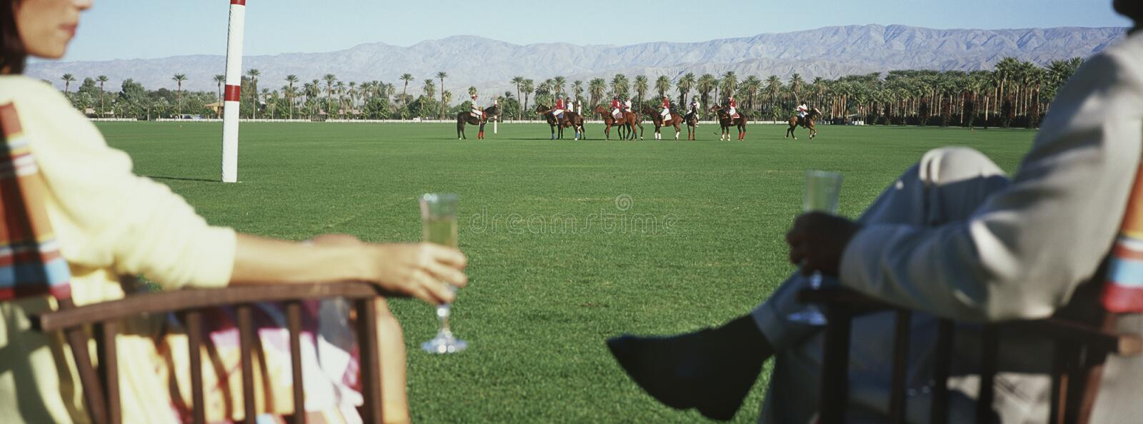 Couple Holding Champagne Flutes While Watching Polo Match. Midsection of couple holding champagne flutes while watching polo match royalty free stock photo