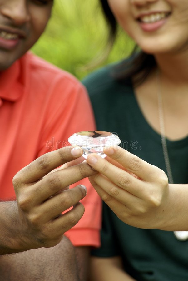 Couple holding a diamond. Ethnic diversity couple with a diamond in their hands. A sign of the committment and friendship that is forever stock photo