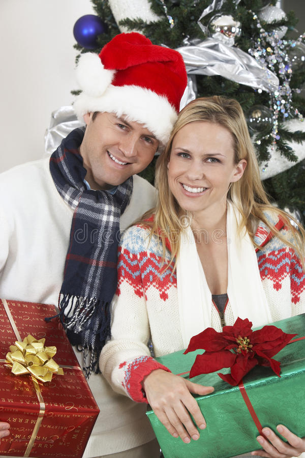 Couple Holding Gifts In Front Of Christmas Tree royalty free stock photos