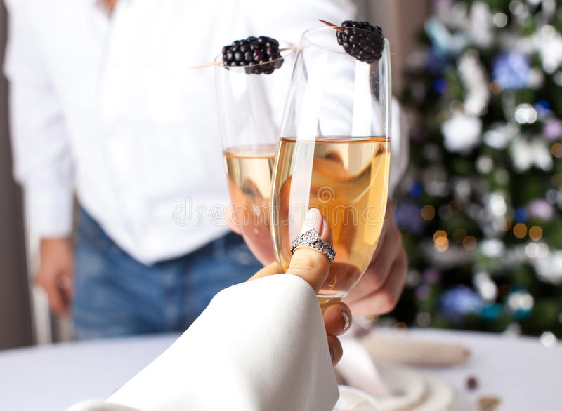 Couple holding glasses of champagne making a toast. stock photos