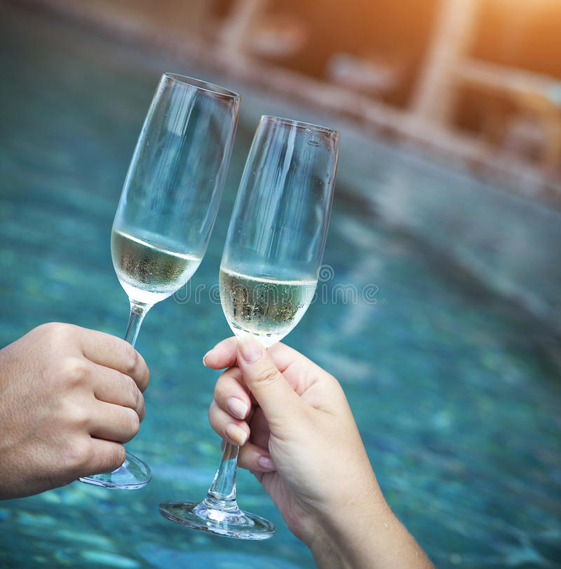 Couple holding glasses of champagne making a toast. By the pool royalty free stock images