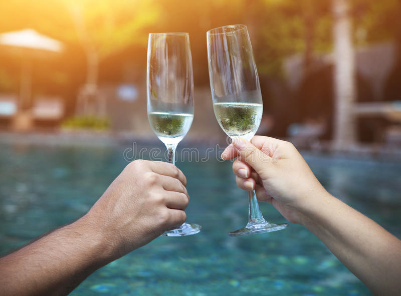 Couple holding glasses of champagne making a toast. By the pool stock image