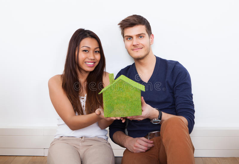 Couple Holding Green House Model At New Home. Portrait of young multiethnic couple holding green house model at new home stock photography
