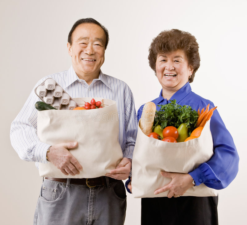 Couple holding grocery bag full of fruit stock image