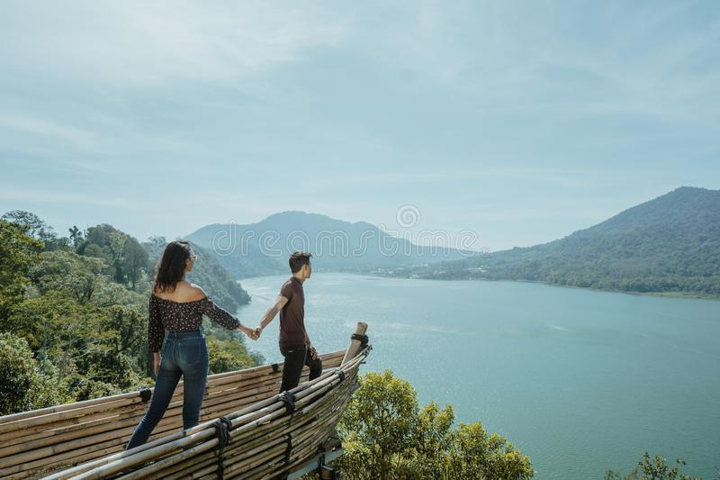 Couple holding hand enjoying nature from hill top stock photo