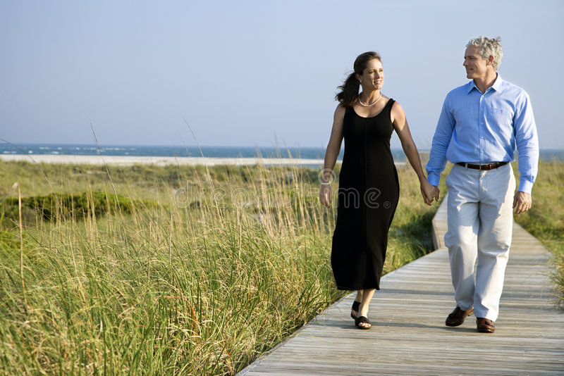 Couple holding hands. Caucasian mid-adult couple holding hands and walking on walkway stock photos