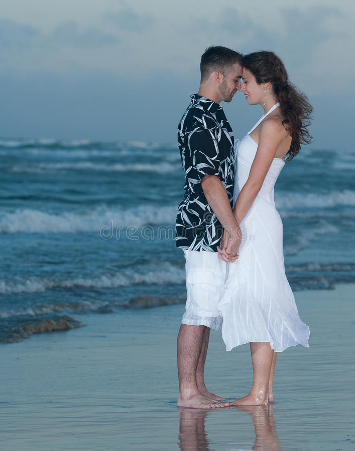 Couple holding hands on beach stock photo