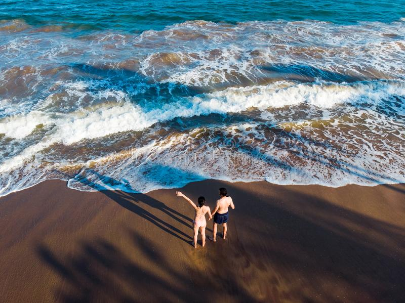 Couple holding hands on the beach aerial royalty free stock photo