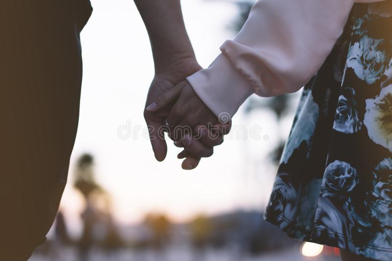 Couple holding for hands on the beach on background ocean sunrise flare, silhouette two romantic people looking on rear view royalty free stock images