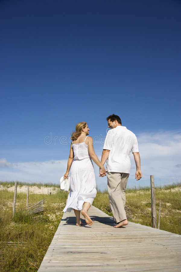 Couple holding hands on beach path. Caucasian mid-adult couple holding hands walking down beach access path royalty free stock photography