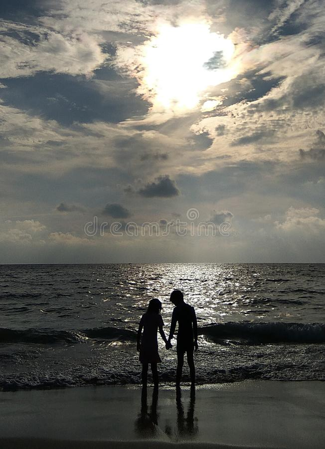 Couple holding hands on the beach. Sunset royalty free stock photo