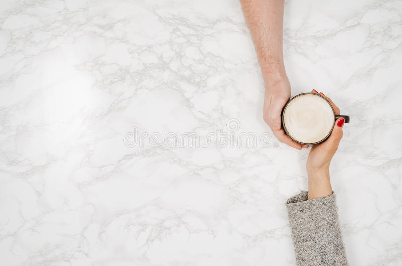 white marble table top. couple holding hands with coffee white marble table, top view table