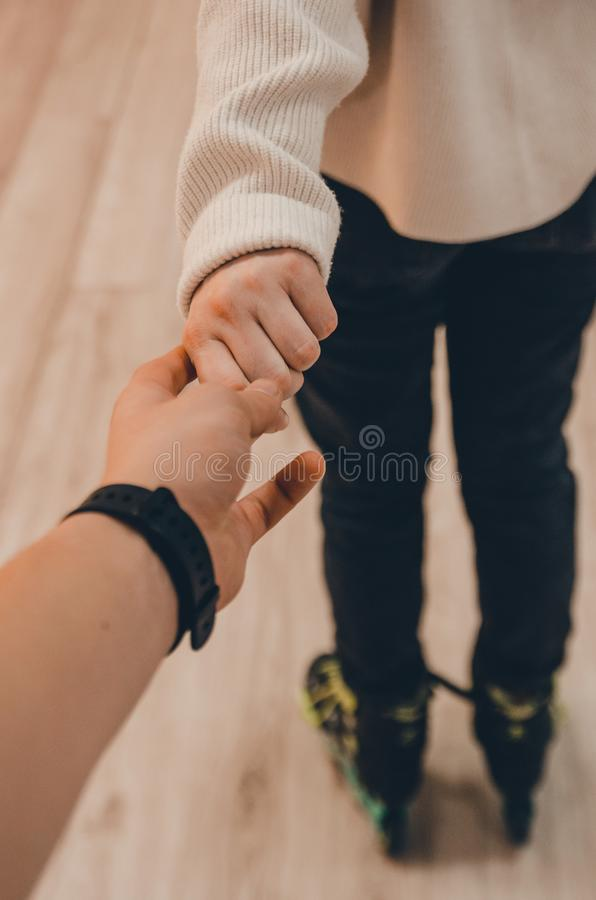 A couple holding hands. Concept close up view. Follow me my love. A romantic date on roller rink in roller skates stock photo