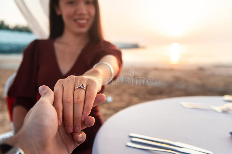 Couple holding hands on a date. Close up, table, dinner, asian, beach, sunset, romantic, romance, summer, two, people, wine, smile, ring, diamond, glass stock photo