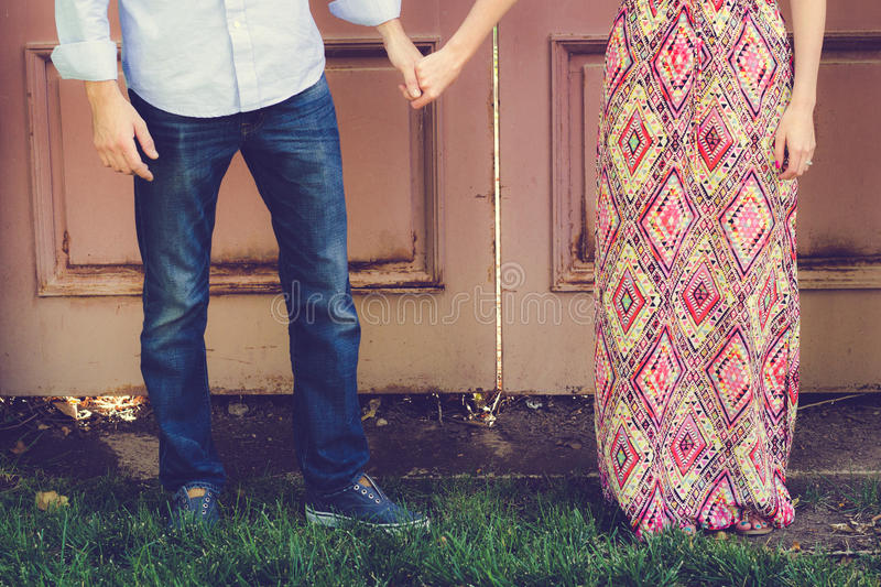 Couple Holding Hands in Front of Antique Door stock photography