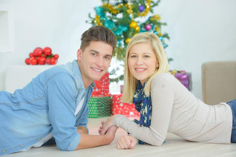Couple holding hands in front Christmas tree stock photos