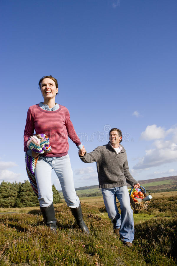 Couple holding hands and having picnic in countryside royalty free stock image