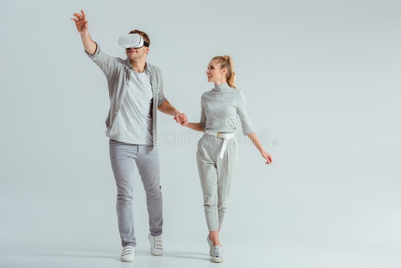 Couple holding hands while man experiencing virtual reality and gesturing. Couple holding hands while men experiencing virtual reality and gesturing on grey royalty free stock photos