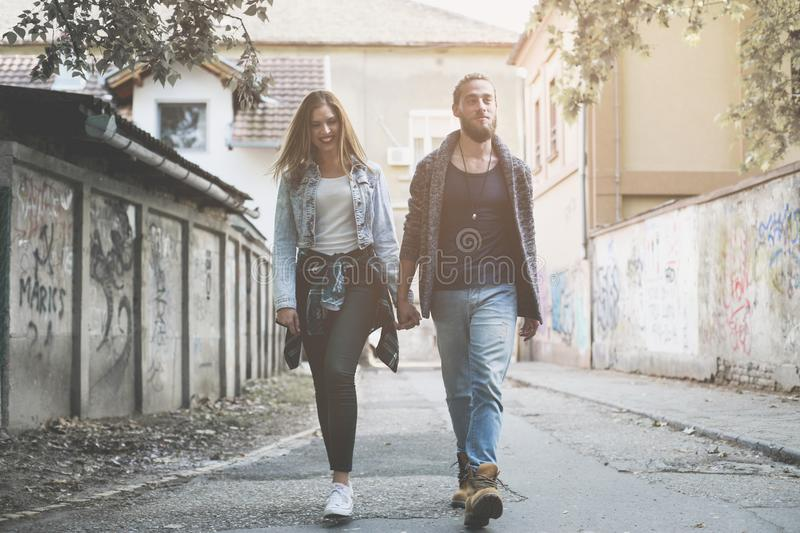 Couple holding hands outdoors. Young couple waling on the street stock photography