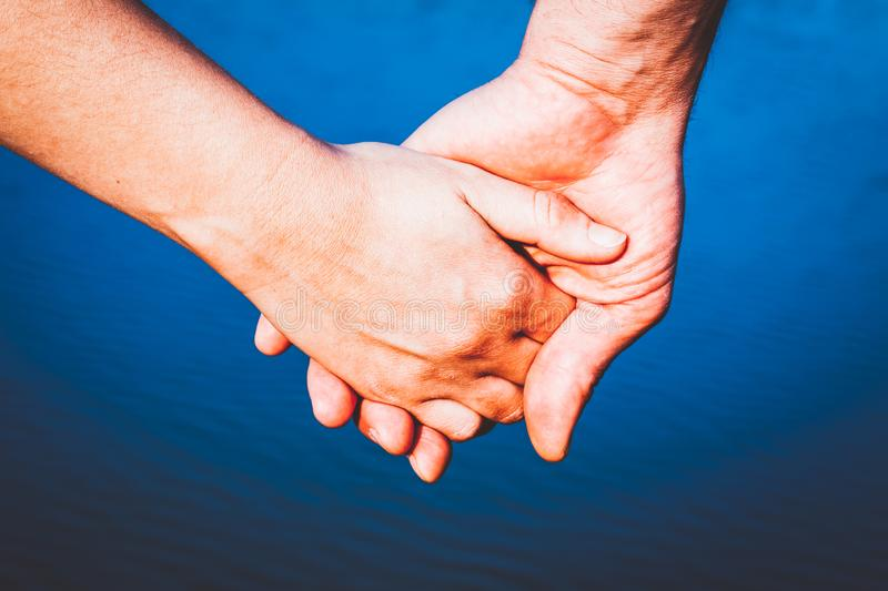 couple holding hands over blue water background stock photo